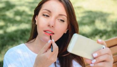 mujer pintando labios smartphone