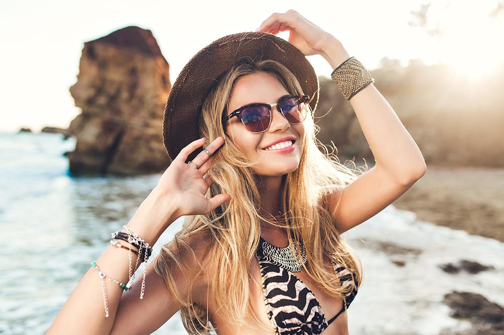 Chica con sombrero y gafas de sol en la playa. Protección solar.