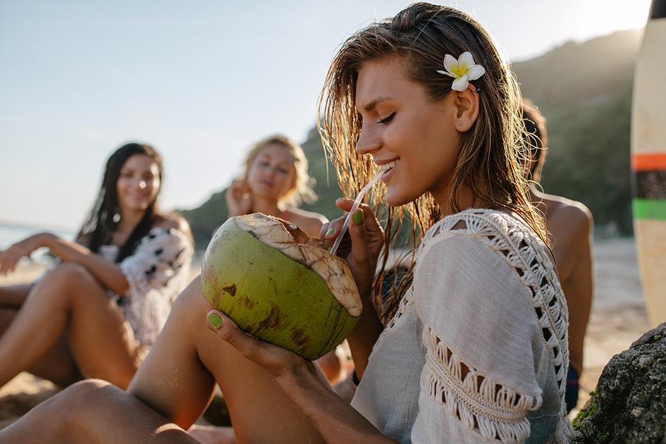 mujer bella bebiendo coco. Aceite de coco