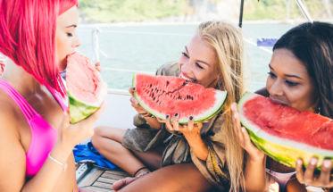 Chicas comiendo sandía en verano. Consejos para no ganar kilos de más estas vacaciones