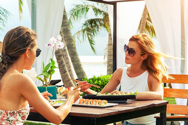 chicas comiendo sushi junto a la playa