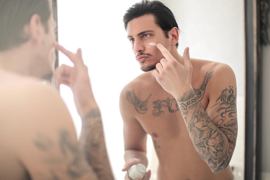 Hombre aplicándose crema facial. belleza hombres