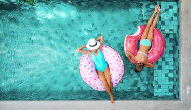 Piscina mujeres con donuts hinchables. Post: dudas protección solar
