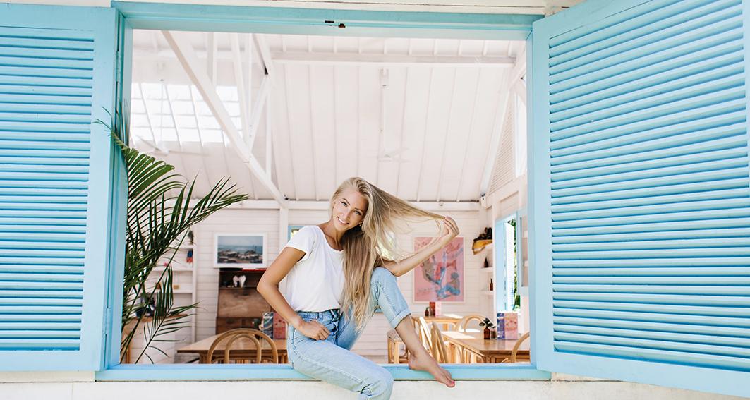 Cabello verano, chica apoyada en una ventana