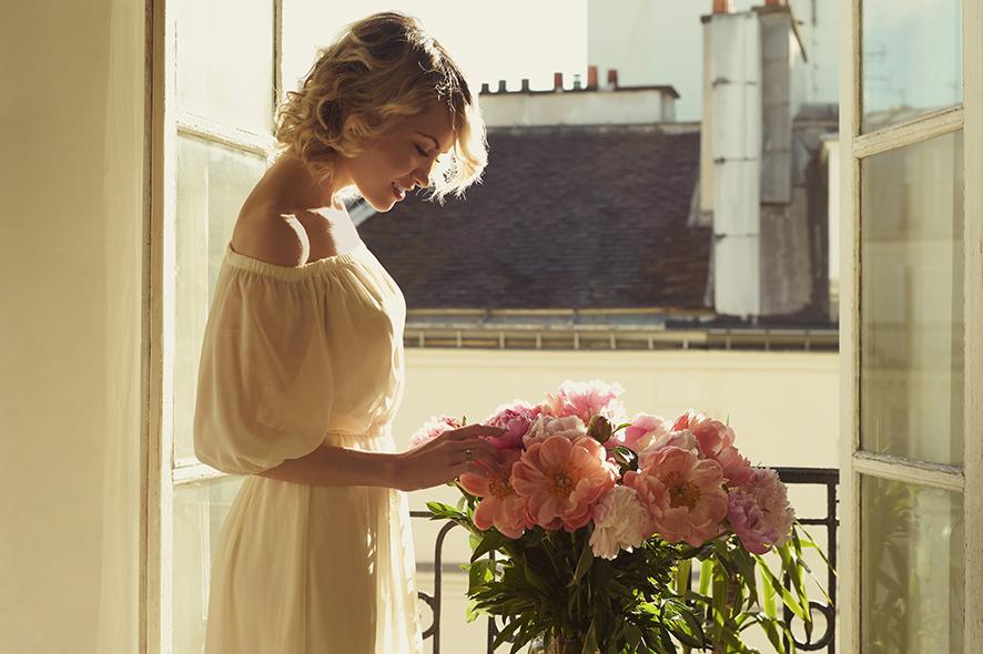 Mujer en una ventana con peonías. Peonía fragancias femeninas.