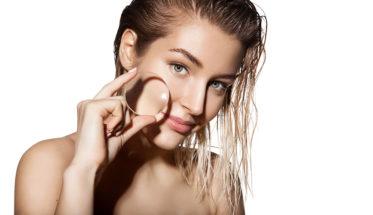 chica joven piel limpia con una lupa. Tratamientos para minimizar los poros