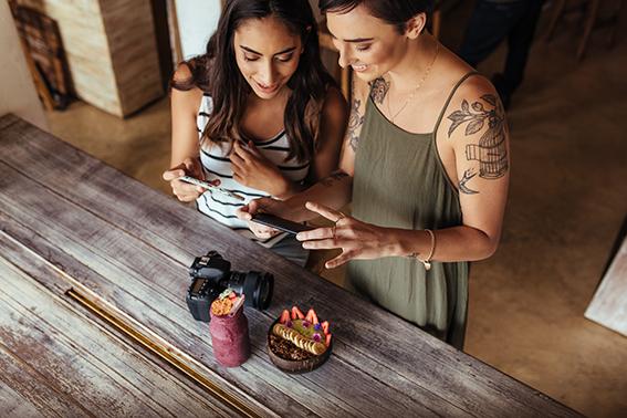 Dos chicas jóvenes hacen fotos con el móvil a un postre