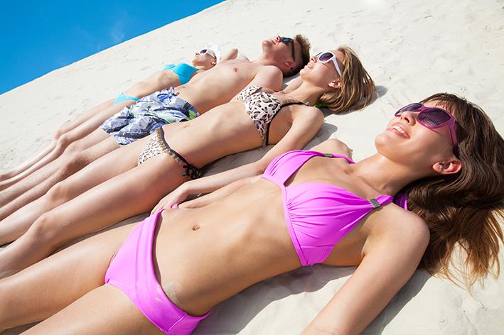 Cuatro adolescentes tumbados al sol en bañador