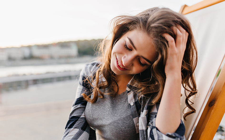 Visual chica tocándose el pelo con la mano para el post 5 tratamientos para darle más volumen a tu cabello