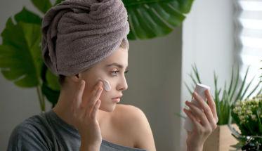 Mujer que se está aplicando crema facial, foto para el artículo sin parabenos