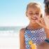 protector solar infantil, imagen de una mujer aplicando crema solar a una niña en la playa