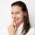 Cuidado facial, mujer joven aplicándose crema en el rostro para el post mejor rutina de cuidado facial