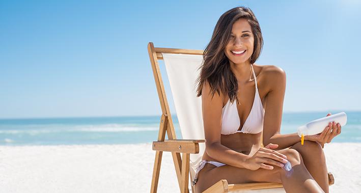 chica con crema de protección solar en la playa