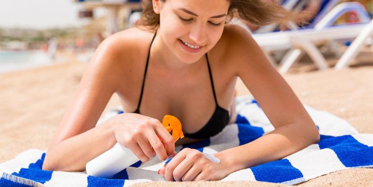 Chica tumbada en la playa aplicándose crema de protección solar para el post cremas solares impiden la síntesis de vitamina D