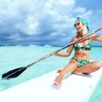 chica practicando paddle surf en el mar para el post de protectores solares minerales
