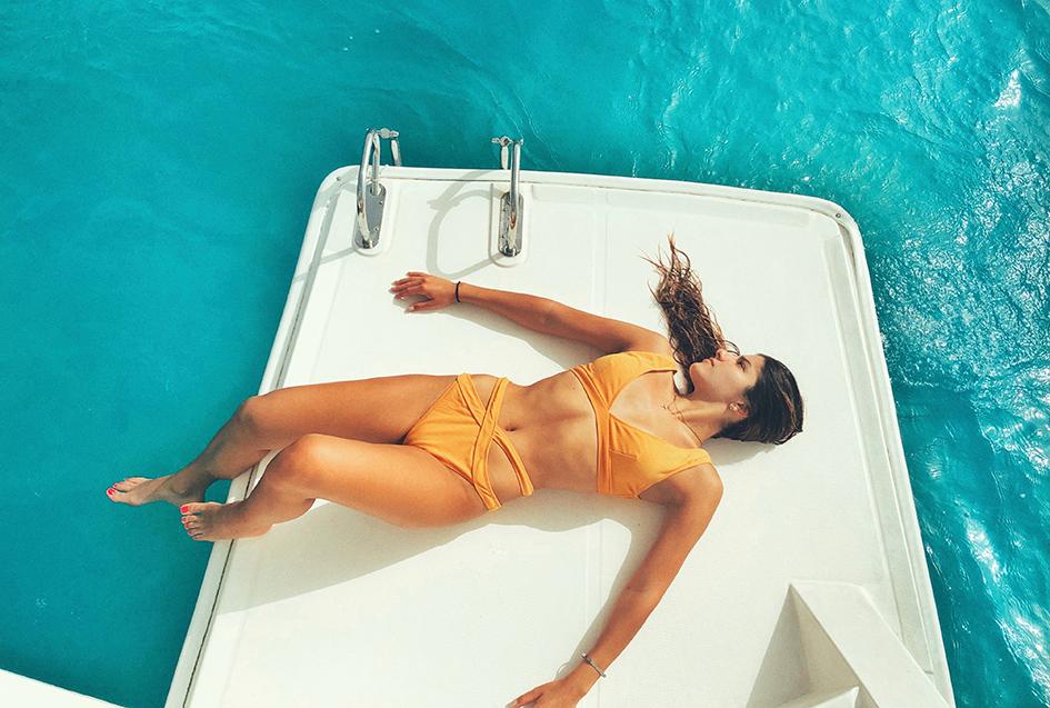 protectores solares minerales, mujer tomando el sol en un barco