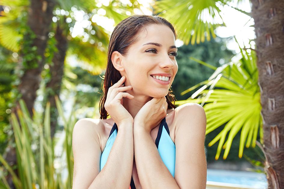Mujer relax en piscina con palmeras para el post cosméticos para pieles estresadas que devuelven el confort a tu piel