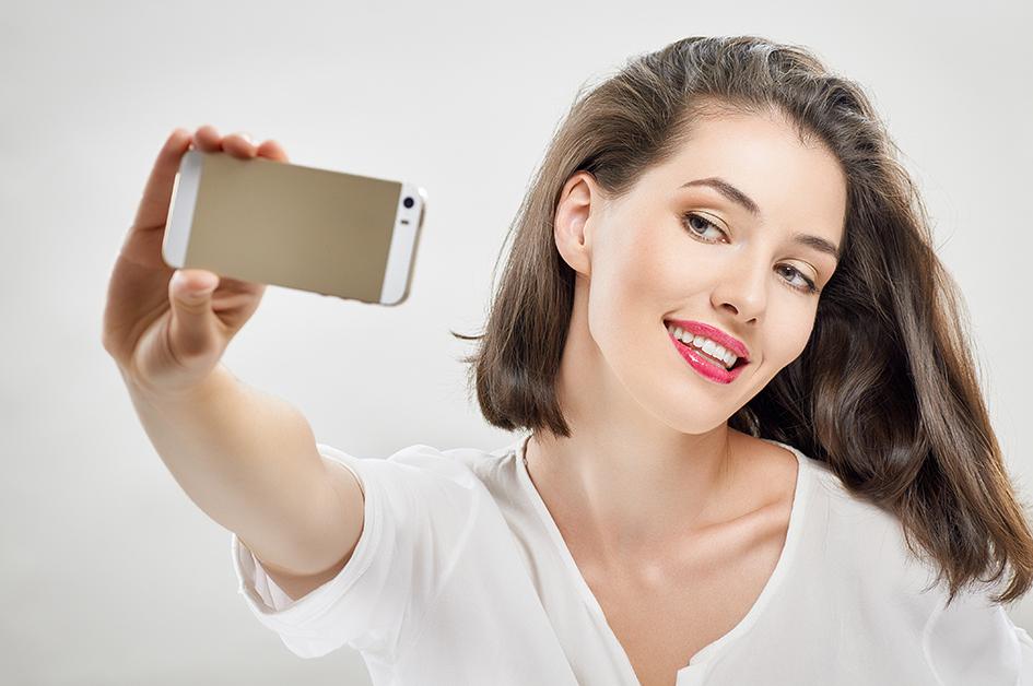 """Mujer haciéndose un selfie con el móvil, para el artículo """"probador virtual de maquillaje"""""""