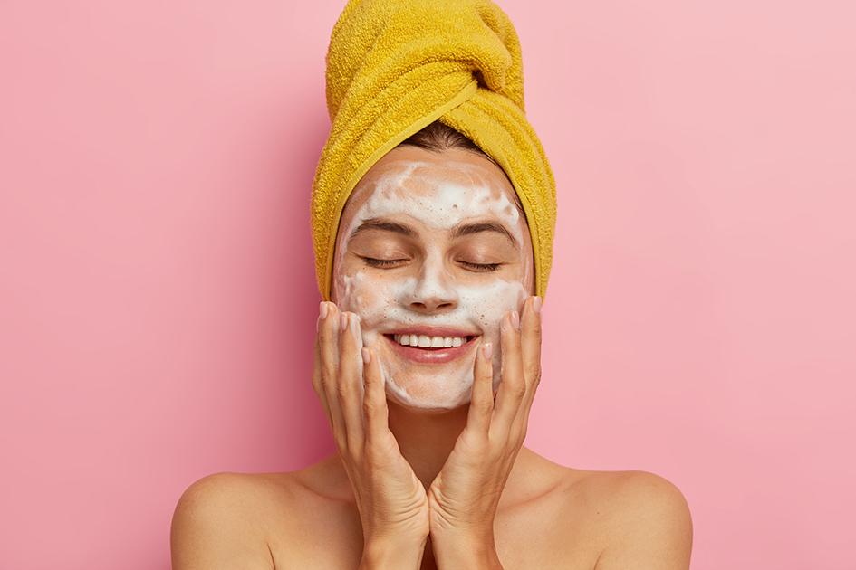 Chica realizando limpieza facial, con una toalla de baño en la cabeza: para el post el mejor limpiador facial de farmacia