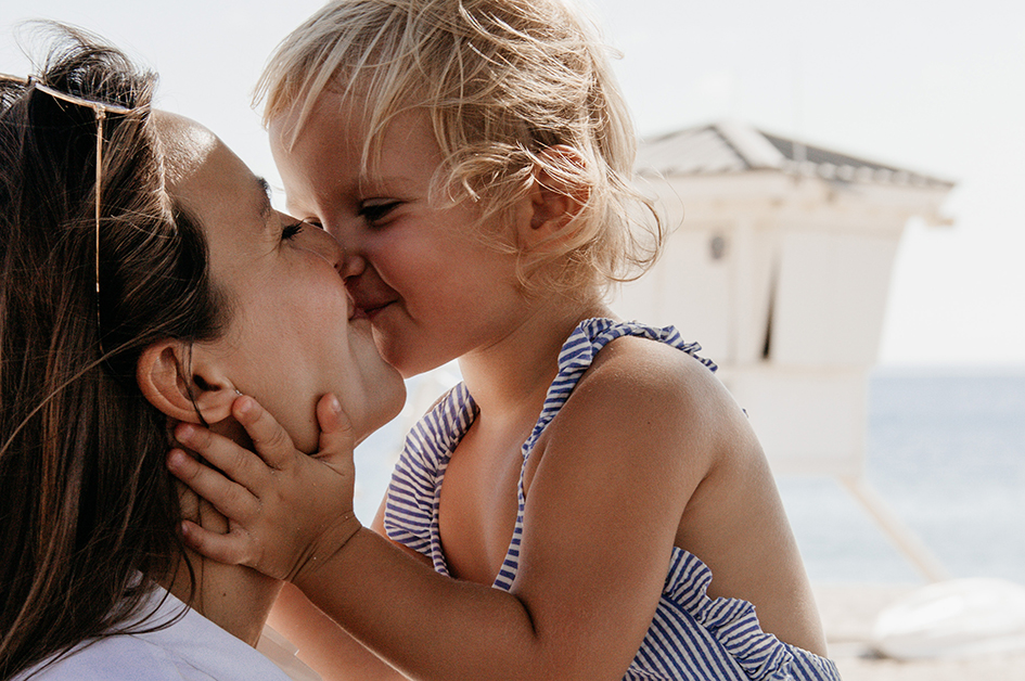 Foto de una madre besando a su hija pequeña para el post: ¿Buscas ideas para regalar un perfume el Día de la Madre? ¡Aquí tienes inspiración!