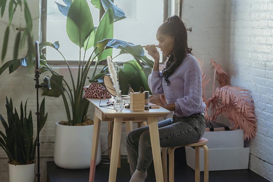 Mujer maquillándose frente a la cámara en un tocador. Imagen para la noticia: tendencias que han revolucionado el sector del lujo en la última década