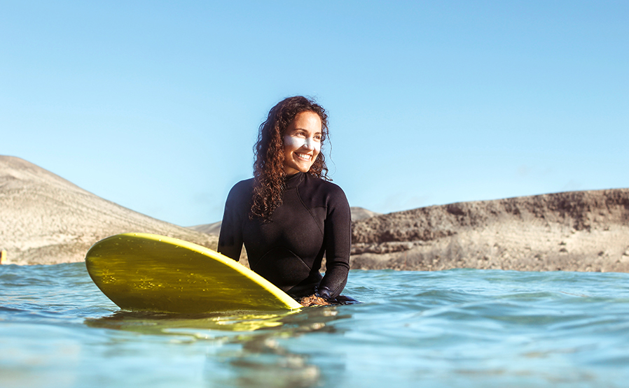 Mujer surfeando en el mar, lleva puesta crema solar en el rostro. Para el artículo: Hablamos sobre protectores solares con cuatro expertas.